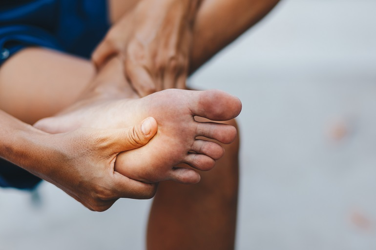 A man holding unto his hurt foot